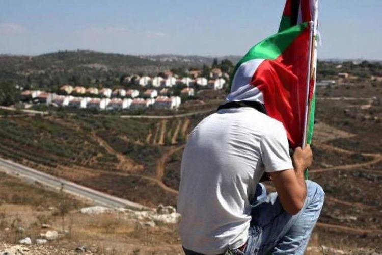 Seorang demonstran duduk sambil memegang bendera Palestina setelah aksi melawan perampasan tanah Palestina untuk memperluas pemukiman Yahudi Hallamish (latar belakang), Jumat (28/8/2015), di Desa Nabi Saleh, Tepi Barat, dekat Ramallah.
