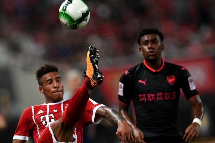 Gelandang Bayern Muenchen, Corentin Tolisso (kiri) dan penyerang Arsenal, Alex Iwobi, berebut bola dalam pertandingan International Champions Cup di Shanghai, Rabu (19/7/2017).