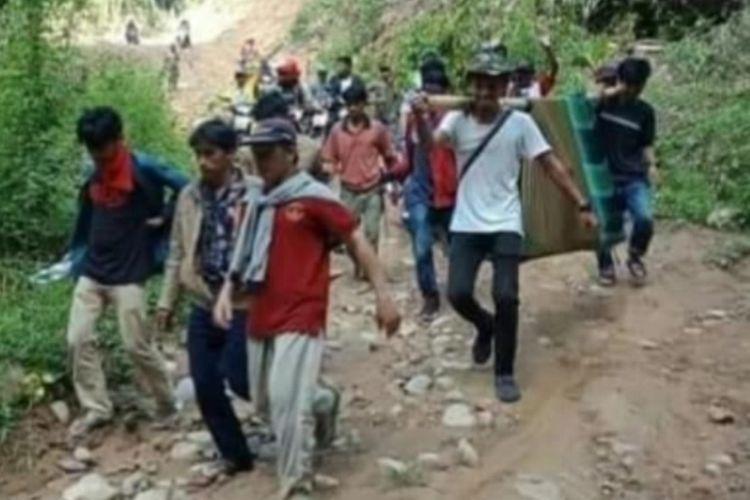 Demi berobat ke puskesmas, seorang warga harus ditandu belasan orang, menyusuri bukit dan sungai, selama tiga hari di Polewali Mandar, Sulawesi Barat, Rabu (13/11/2019). Hal ini terjadi lantaran jalan setapak dari desa tersebut ke kota kecamatan tidak bisa dilalui kendaraan.
