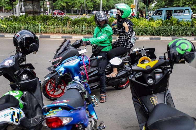 Pengemudi ojek online dengan penumpangnya di Stasiun Karet, Jakarta Pusat, Senin (8/6/2020). Pemerintah Provinsi DKI Jakarta mengizinkan pengemudi ojek online beroperasi untuk mengangkut penumpang selama PSBB transisi dengan menerapkan protokol kesehatan.