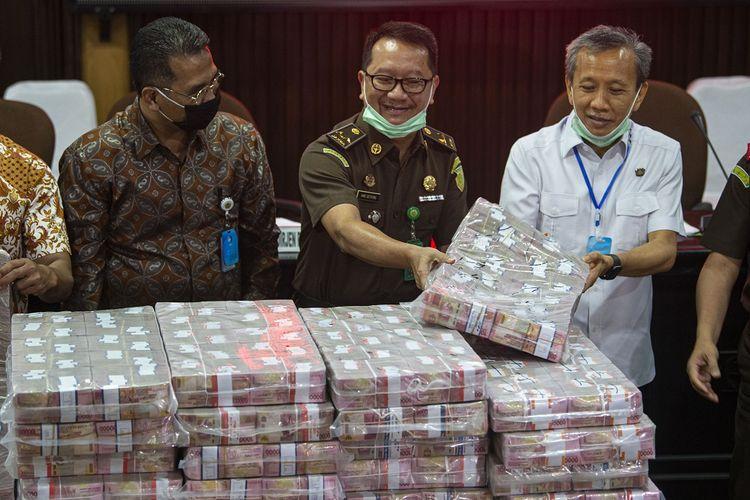 Kepala Pusat Penerangan Hukum (Kapuspenkum) Kejaksaan Agung (Kejagung) Hari Setiyono (tengah) dan Jaksa Agung Muda Pidana Khusus (Jampidsus) Ali Mukartono (kanan), dan Direktur Jenderal Perbendaharaan Kemenkeu Andin Hadiyanto menunjukkan barang bukti berupa uang sitaan di kantor Kejagung, Jakarta, Selasa (7/7/2020). Kejagung mengeksekusi kilang LPG PT TLI di Tuban Jawa Timur dan uang senilai Rp 97 miliar hasil korupsi terpidana penjualan kondensat di BP Migas Honggo Wendratno, serta uang sebesar Rp73,9 miliar dalam perkara dugaan tindak pidana korupsi pengelolaan keuangan dan dana investasi pada PT Asuransi Jiwasraya (Persero) tahun 2008-2018. ANTARA FOTO/Aditya Pradana Putra/foc.