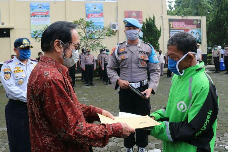 Ketua DPRD Banyumas Budhi Setiawan menyerahkan santunan untuk Mulyono di halaman Mapolresta Banyumas, Jawa Tengah, Selasa (7/4/2020).