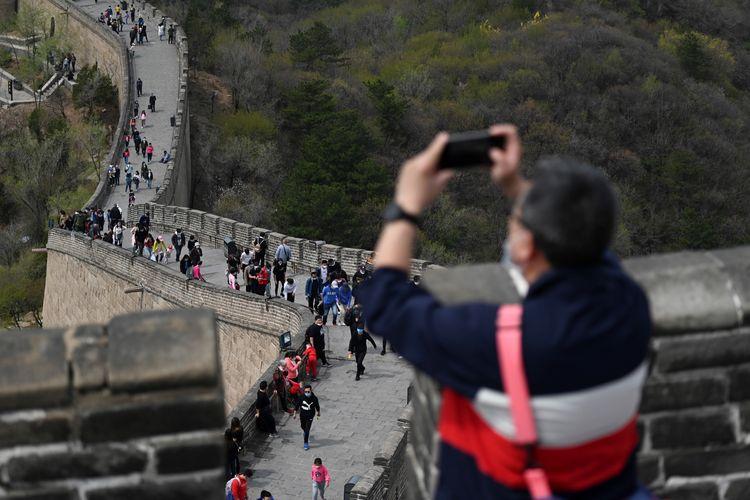 Pengunjung mengenakan masker untuk menghindari tertular Covid-19, saat mengunjungi Tembok Besar China, di Beijing, 18 April 2020. Setelah sempat menjalani masa karantina akibat penyebaran Covid-19, jutaan orang di China kembali turun ke jalan dan mengunjungi kawasan wisata yang kembali dibuka.