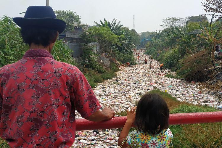 Warga menyaksikan operasi pengangkutan sampah di Kali Jambe, Kabupaten Bekasi, Jumat (6/9/2019).