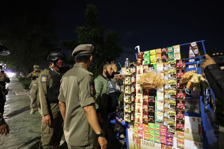 Petugas gabungan melakukan penertiban kepada pedagang kaki lima (PKL) di sepanjang Jalan Danau Sunter Selatan, Tanjung Priok, Jakarta Utara, Kamis (11/2/2021) malam.