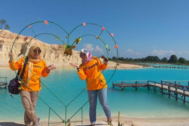 Wisatawan berpose di ornamen buatan yang disediakan pengelola di Gurun Telaga Biru Bintan, Kepulauan Riau, belum lama ini.
