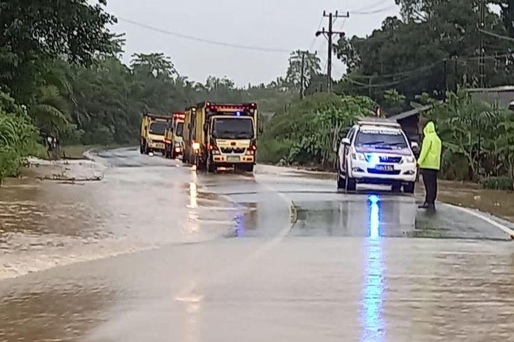 Petugas kepolisian dari Polsek Satui, Kabupaten Tanah Bumbu, Kalsel, mengatur arus lintas di Jalur Trans Kalimantan yang terendam banjir akibat tingginya intensitas hujan pada, Kamis (12/8/2021).