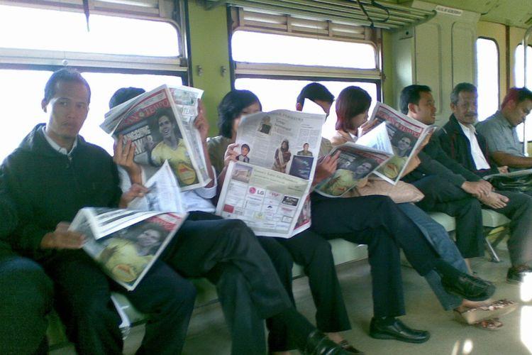 Potret penumpang KA PRameks yang tengah membaca koran di tengah perjalanan kereta