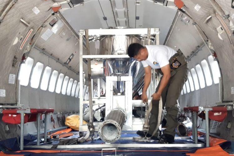 Seorang prajurit TNI AU tengah mempersiapkan tabung berisikan garam yang akan disemai ke atmosfer.