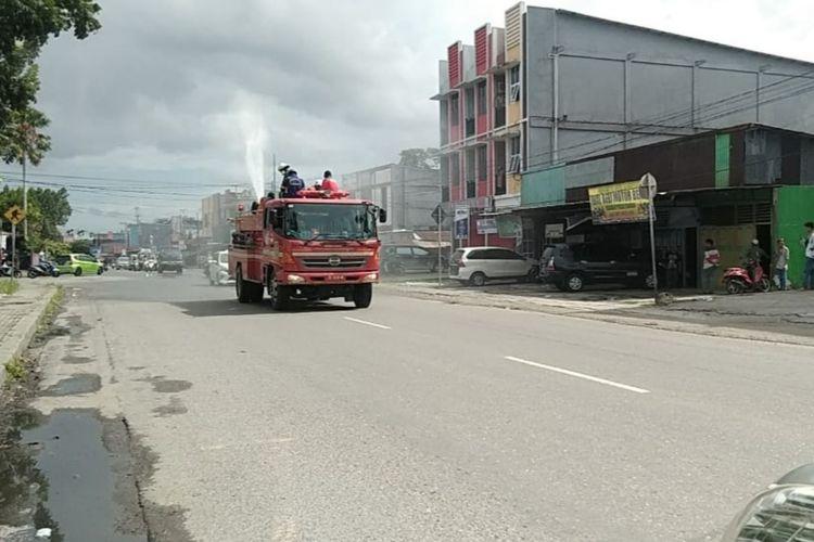 Petugas pemadam kebakaran melakukan penyemprotan disinfektan di Jalan Budi Utomo, Kamis (26/3/2020).