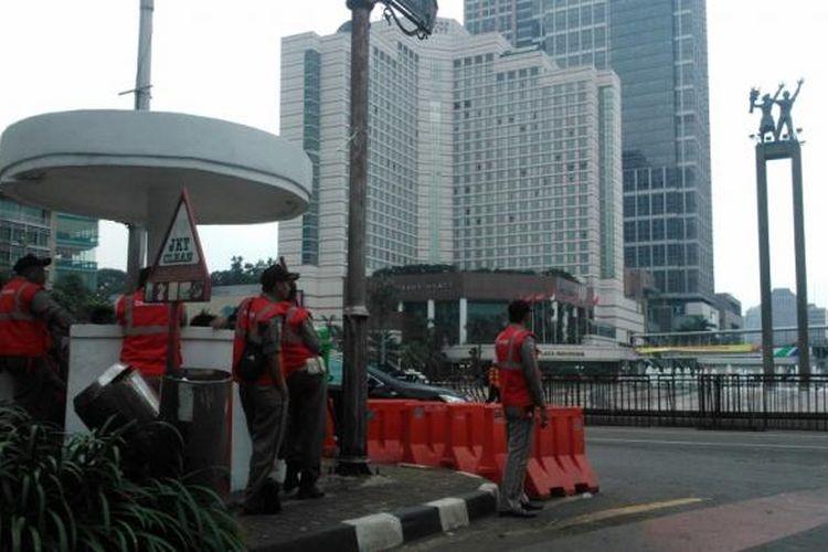 Sejumlah petugas transjakarta memanfaatkan waktu luang berkumpul di pos saat operasional bus koridor I dihentikan sementara, Jumat (1/5/2015) siang.