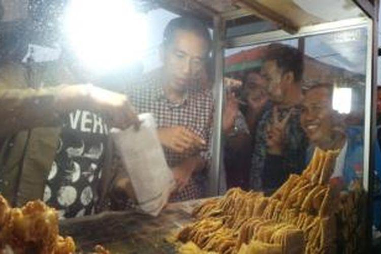 Calon presiden Joko Widodo membeli gorengan untuk berbuka puasa di pinggir Jalan Ir H Juanda, Bekasi, Jumat (4/7/2014).