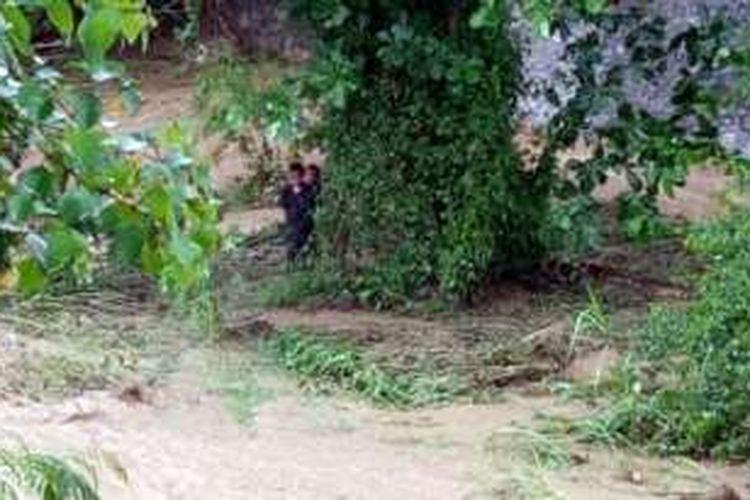 Dua dari 4 anak terlihat berlindung di balik pohon saat sungai Hutuo meluap tiba-tiba. 2 teman lainnya ditemukan meninggal dunia dan satu hilang diseret air bah.