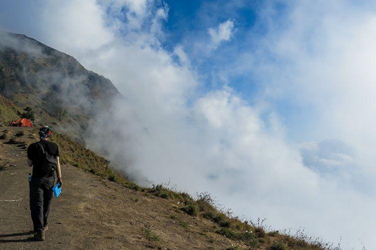 Seorang pendaki Gunung Rinjani berjalan di samping awan di Plawangan Sembalun.