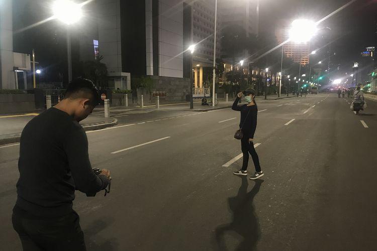 Warga berfoto di Jalan MH Thamrin yang masih ditutup untuk kendaraan, Jumat (24/5/2019).
