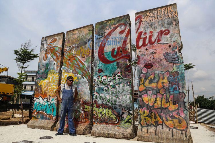 Seniman Teguh Ostenrik berpose didepan batu pecahan tembok berlin di kawasan Ruang Publik Terpadu Ramah Anak (RPTRA) dan Ruang Terbuka Hijau (RTH) Kalijodo, Jakarta Barat, Selasa (26/9/3017). Karya seni instalasi ini bernama Patung Menembus Batas terdiri dari empat pecahan tembok Berlin dan 14 patung baja hasil karya dari seniman Teguh Ostenrik.