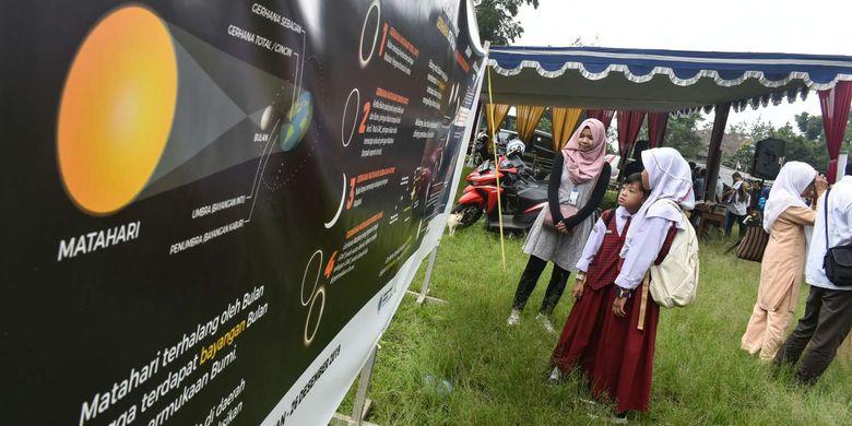 Siswa sekolah dasar tengah memperhatikan infografis dan penjelasan dari seorang penutur Observatorium Boscha terkait Gerhana Matahari, Kamis (26/12/2019).