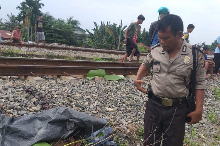 Seorang petugas polisi berdiri di dekat jenazah Ferri Pasaribu di pinggir rel kereta api. Sebelumnya, seorang saksi mata menyebut Ferri awalnya berdiri di dekat rel. Saat kereta api melaju kencang, korban melompat ke arah rel.