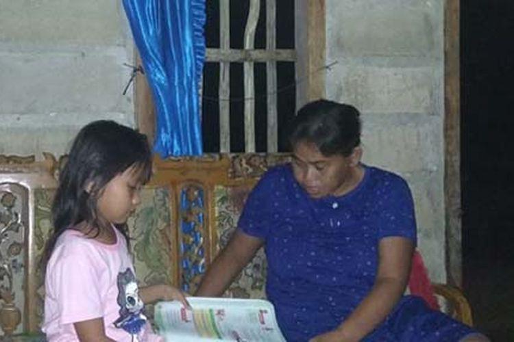 Rafika didampingi sang Ibu saat melakukan belajar dari rumah. Rafika terpaksa harus menumpang di rumah tetangganya demi bisa belajar daring.