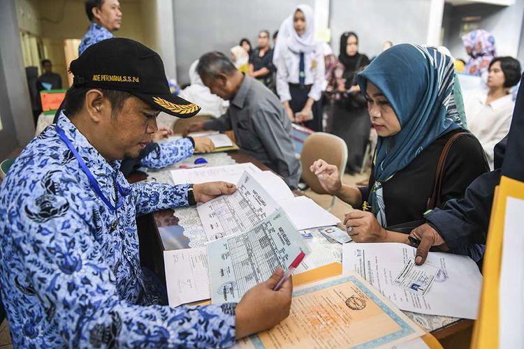 Petugas memeriksa berkas pendaftaran Penerimaan Peserta Didik Baru (PPDB) 2019 tingkat SMA-SMK di SMAN 2 Bandung, Jawa Barat, Senin (17/6/2019). Kuota Penerimaan Peserta Didik Baru (PPDB) SMA Jawa Barat periode 2019/2020 sebanyak 281.950 kursi dan pendaftarannya dimulai serentak 17 Juni hingga 22 Juni 2019.