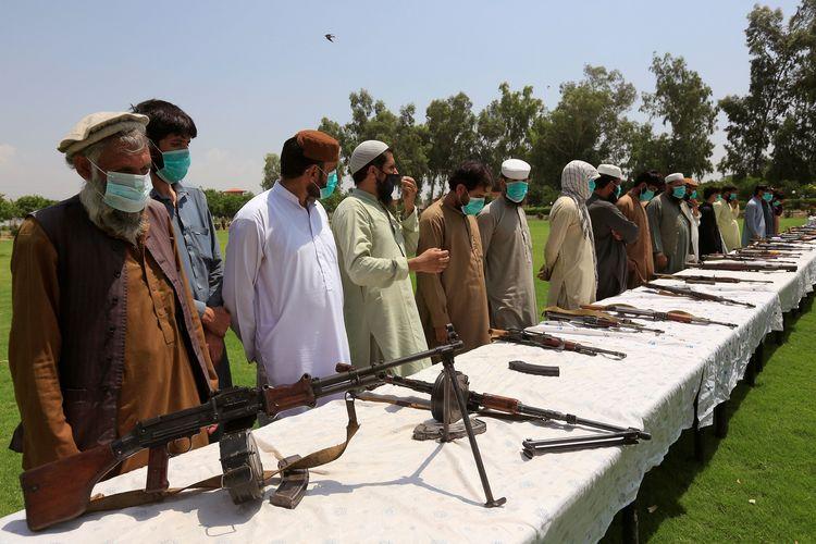 Para anggota Taliban menyerahkan senjata mereka dan bergabung dengan upaya rekonsiliasi serta reintegrasi dari pemerintah Afghanistan di Jalalabad, 25 Juni 2020.