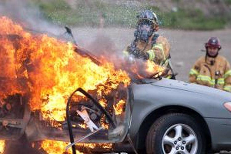 Ilustrasi: petugas berusaha memadamkan kobaran api pada mobil.