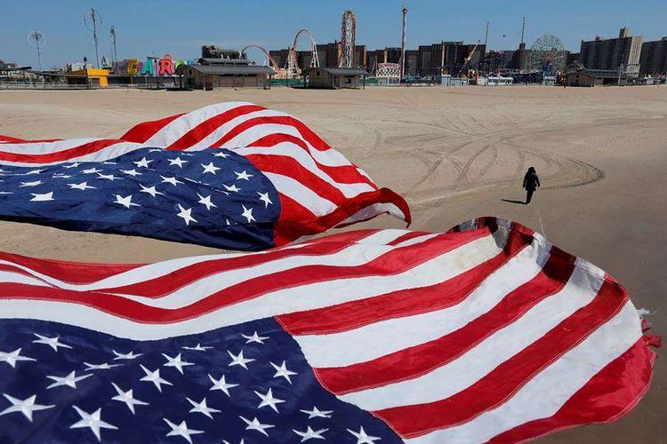 Seseorang berjalan dibawah bendera Amerika Serikat di pantai Pulau Coney saat mewabahnya virus corona (Covid-19), di Brooklyn, New York, Amerika Serikat, Minggu (19/4/2020). Berdasarkan data Johns Hopkins University, hingga Selasa (21/4/2020), AS masih menjadi negara dengan kasus Covid-19 tertinggi dunia mencapai 787.794 dengan korban meninggal 42.362.