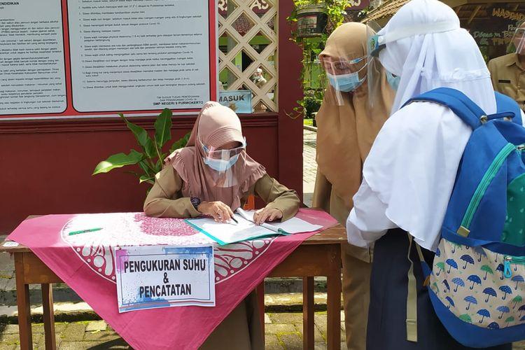 Tes suhu tubuh bagi siswa sebelum masuk di SMP Negeri 9 Purwokerto, Kabupaten Banyumas, Jawa Tengah, Senin (5/4/2021).