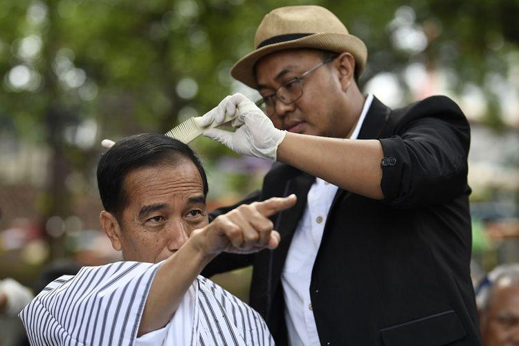 Presiden Joko Widodo (kiri) mengikuti potong rambut massal di area wisata Situ Bagendit, Garut, Jawa Barat, Sabtu (19/1/2019). ANTARA FOTO/Puspa Perwitasari/foc.