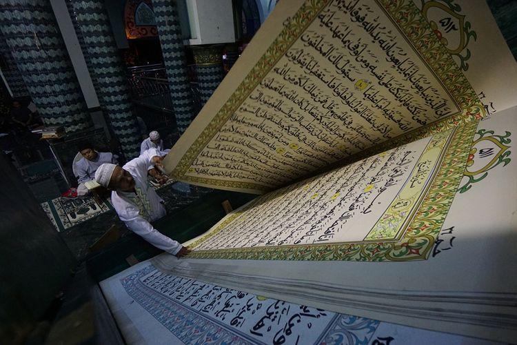 Kegiatan tadarus menggunakan Al Quran raksasa di Masjid Baiturrahman, Banyuwangi, Minggu (4/6/2017). Al Quran setinggi 210 sentimeter dan lebar 140 sentimeter itu dibuat selama 6 bulan dengan menggunakan kertas khusus, 32 dus spidol kualitas terbaik dan tinta lebih dari 40 dus.