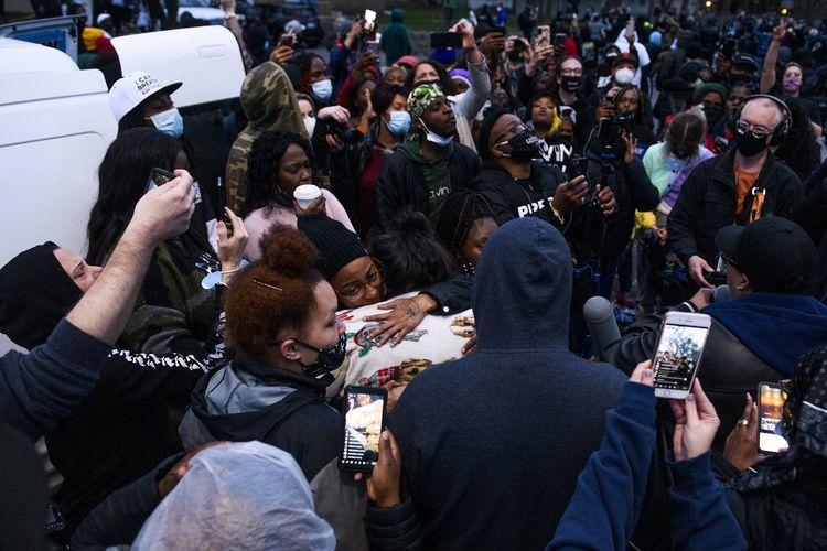 Orang-orang mengerubungi Katie Wright (tengah), ibu Daunte Wright (20) pria kulit hitam yang ditembak mati polisi Minneapolis pada Minggu (11/4/2021) di Brooklyn Center, Minnesota, Amerika Serikat. Penembakan ini kembali memicu demo di Minneapolis.