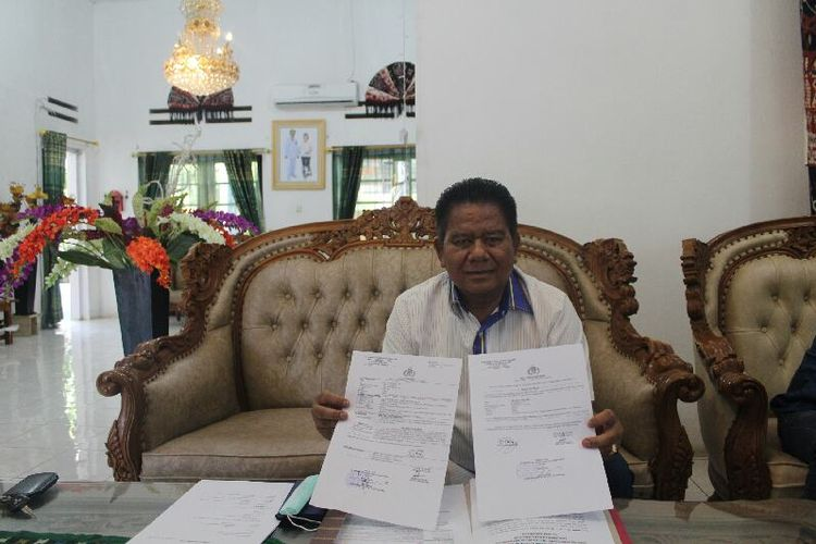 Bupati Sumba Timur, Gidion Mbilijora menunjukkan surat laporan polisi atas dugaan pencemaran nama baik terhadap dirinya oleh ketua DPRD Kabupaten Sumba Timur, Nusa Tenggara Timur, Sabtu (18/7/2020).
