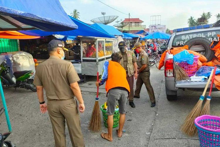Seorang warga melakukan kerja sosial menyapu jalan setelah terjaring tidak memakai masker