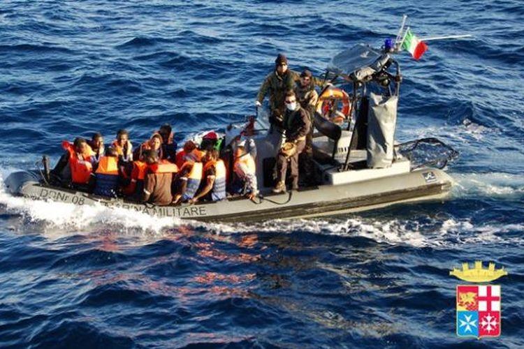 Dalam foto yang dirilis Angkatan Laut Italia ini terlihat sebuah perahu motor AL Italia membawa sejumlah imigran gelap yang diselamatkan di dekat Pulau Lampedusa, Italia pada Kamis (2/1/2014).