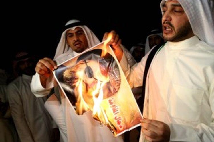 Sejumlah warga Kuwait membakar foto pemimpin Hezbollah, Hassan Nasrallah dalam aksi unjuk rasa di depan Kedutaan Besar Lebanon di Kuwait.