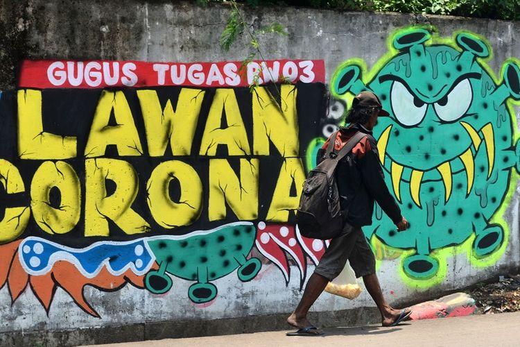 Warga melintas di depan mural berisi ajakan melawan corona di Jalan Pahlawan Komarudin RW 03, Cakung Barat, Jakarta Timur, Sabtu (17/10/20). Visual karya Komunitas Bale Buku tersebut mengusung tema Sosialisasi Protokol Kesehatan 3 Msebagai imbauan kepada masyarakat pentingnya protokol kesehatan memakai masker, menjaga jarak, dan mencuci tangan untuk mencegah penyebaran penularan COVID-19. ANTARA FOTO/Suwandy/hp.