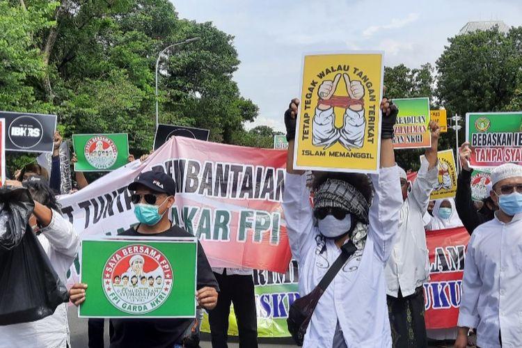 Massa ANAK NKRI membentangkan poster di Jalan Merdeka Selatan, Jumat (18/12/2020)