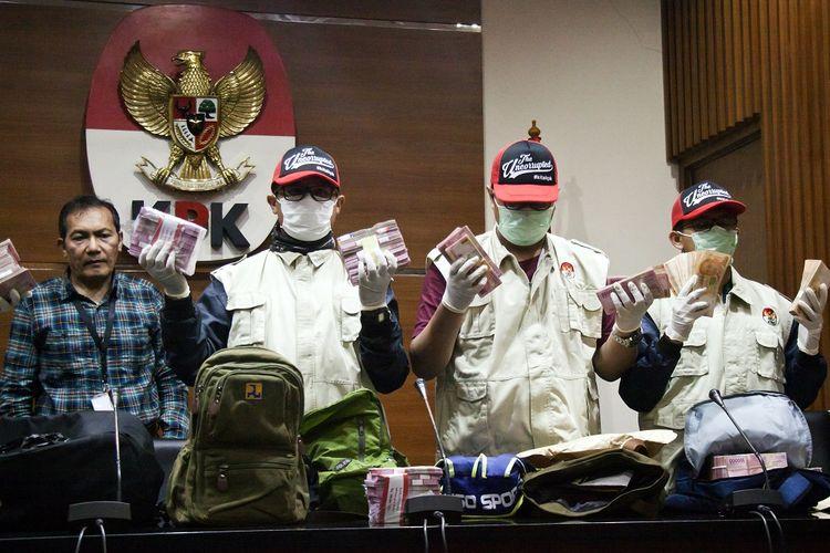Wakil Ketua KPK Saut Situmorang (kiri) menyaksikan penyidik menunjukkan barang bukti uang saat konferensi pers mengenai Operasi Tangkap Tangan (OTT) kasus korupsi pejabat Kementerian Pekerjaan Umum dan Perumahan Rakyat (PUPR) dengan pihak swasta, di Gedung KPK, Jakarta, Minggu (30/12/2018) dini hari. Dari OTT tersebut KPK menyita barang bukti uang dalam tiga pecahan mata uang sebesar 3.200 dolar AS, 23.100 dolar Singapura, dan Rp3,9 miliar, serta menangkap 20 orang terkait proyek sistem penjernihan air minum (SPAM) Ditjen Cipta Karya tahun 2018 di sejumlah daerah. ANTARA FOTO/Galih Pradipta/kye.