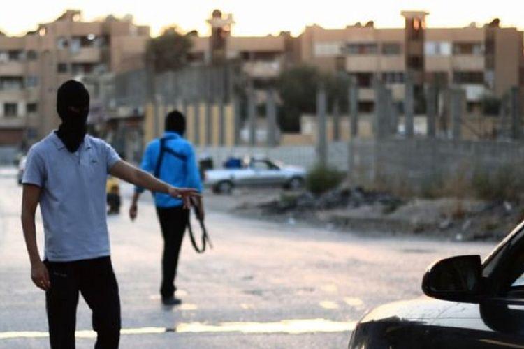 Dua orang anggota polisi ISIS menghentikan kendaraan di salah satu titik kota Raqqa, Suriah utara.