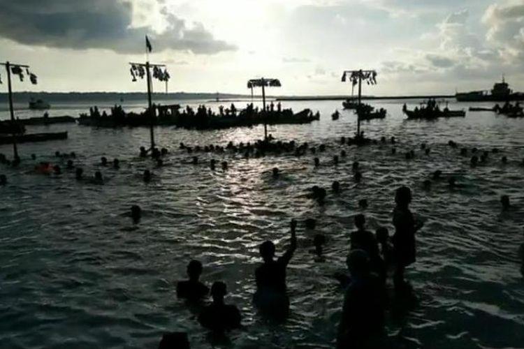 Puluhan anak-anak berlomba berenang  mendekati dan memanjat sebatang kayu yang ditancapkan dari atas laut, Minggu (18/11/2018). Terlihat beberapa kali anak kecil tersebut terjatuh karena batang kayu tersebut licin. Ini merupakan perlombaan panjat pinang yang dilakukan puluhan anak-anak di Kecamatan Wangiwangi, Kabupaten Wakatobi, Sulawesi Tenggara.