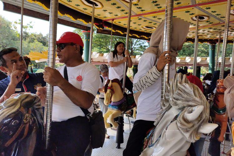 Penyandang disabilitas ketika naik wahana Turangga-rangga di Dufan, Ancol, Jakarta Utara, Selasa (3/12/2019) kala merayakan hari disabilitas internasional.
