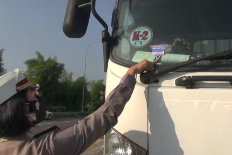 Polisi menempelkan stiker kendaraan sektor esensial atau kritikal yang diperbolehkan lewat setelah melewati pemeriksaan di Pos Polisi Exit Tol Brebes Timur, Jumat (16/7/2021) (Istimewa)