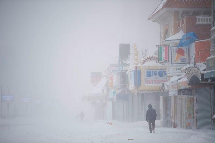 Seorang pria berjalan di atas papan kayu yang tertutup salju saat badai salju pada Kamis (4/1/2018), di Atlantic City, New Jersey. (AFP/Mark Makela)