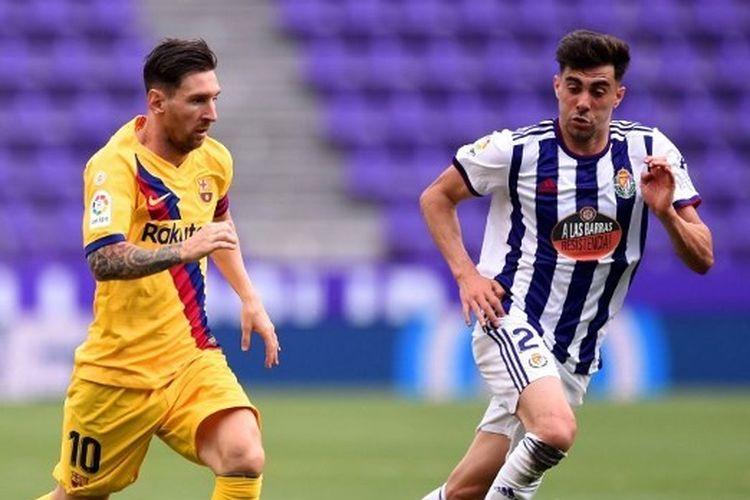 Lionel Messi mencoba melewati Kike Perez dalam laga Real Valladolid vs Barcelona pada lanjutan pekan ke-36 Liga Spanyol yang dilangsungkan di Stadion Jose Zorilla, Minggu (12/7/2020).