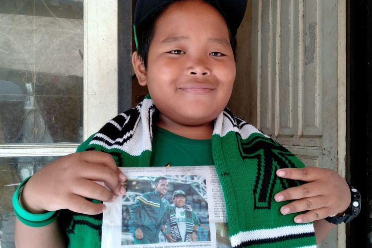 Deni memperlihatkan fotonya bersama pemain Persebaya Surabaya Irfan Jaya yang terpampang di salah satu media cetak.