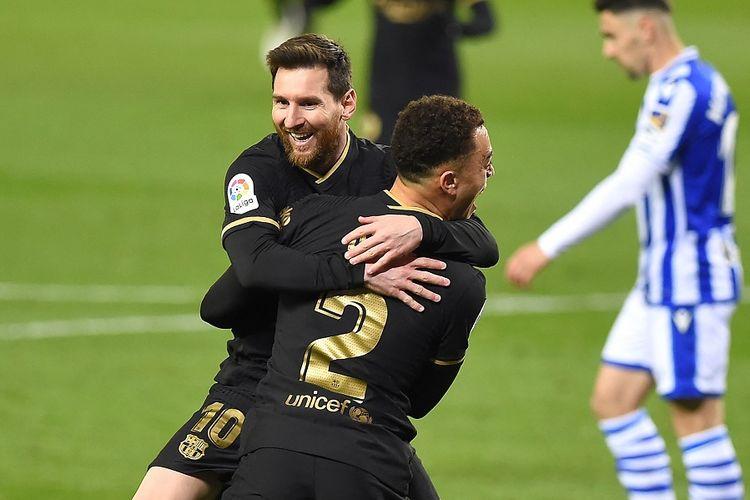Bek Barcelona, Sergino Dest, merayakan gol dengan Lionel Messi (punggung) setelah mencetak gol dalam pertandingan Liga Spanyol antara Real Sociedad vs Barcelona di Stadion Anoeta di San Sebastian pada 21 Maret 2021.