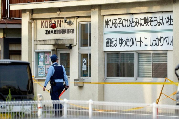 Polisi berjaga di depan pos polisi Toyama, Jepang, setelah seorang pelaku menusuk dan membunuh polisi di sana, serta menembak mati petugas keamanan sekolah dekat pos Selasaa (26/6/2018).
