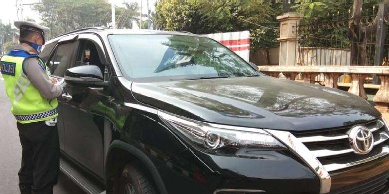 Polisi memberhentikan sebuah mobil bermerek Toyota Fortuner berwarna hitam dengan pelat nomor B 100 NAR di ruas Jalan MT Haryono ke arah Jalan Gatot Subroto, Jakarta, Rabu (1/8/2018). Petugas kepolisian mulai memberlakukan penindakan berupa tilang terhadap pengendara mobil yang melanggar di kawasan perluasan sistem ganjil-genap.