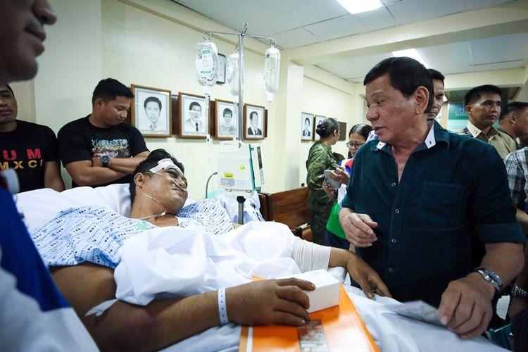 Presiden Filipina Rodrigo Duterte menengok seorang prajurit yang terluka akibat pertempuran melawan militan di kota Marawi.