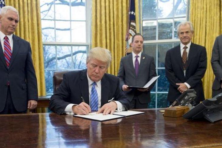 Presiden AS Donald Trump menandatangani sejumlah perintah eksekutif di ruang Oval, Gedung Putih disaksikan wakil presiden Mike Pence, kepala staf Gedung Putih Reince Preibus, dan penasihat senior Jared Kushner.
